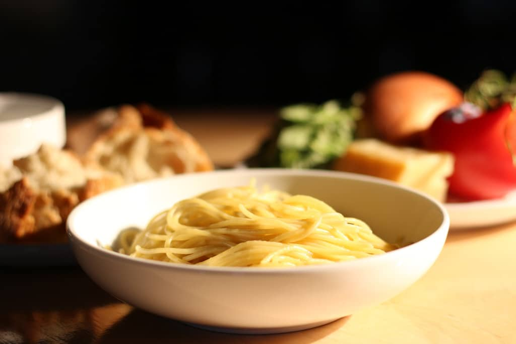 A bowl of pasta surrounded by bread and items to make sauce